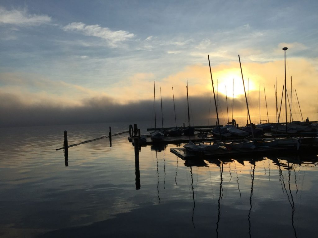 The sun rising through mist over boats on still water.