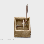 bronze box sculpture with nail sicking out